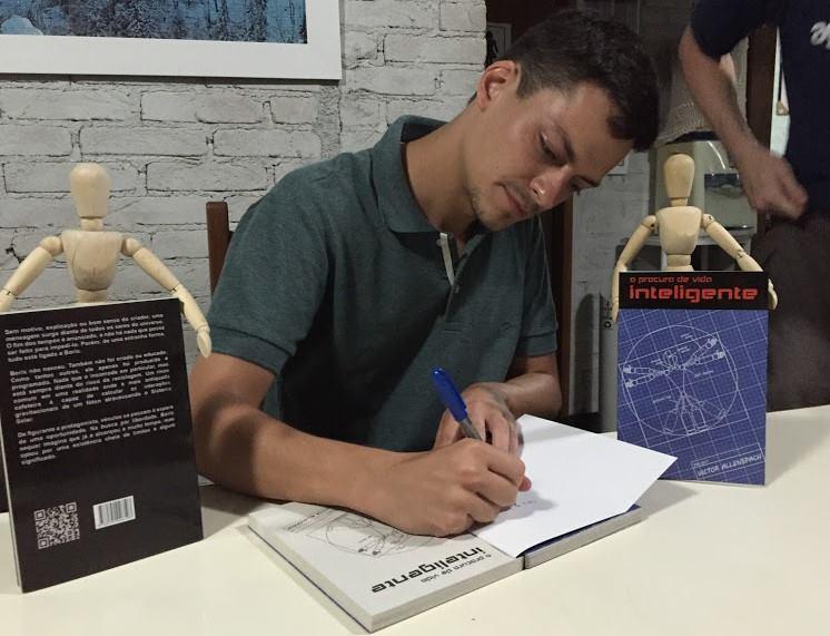 O autor com as suas obras em uma sessão de autógrafos.